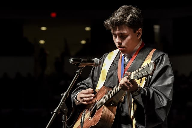 Edison graduate playing guitar